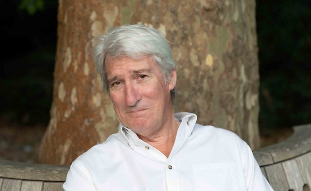 Jeremy Paxman smiles for a photo sitting in front of a tree.