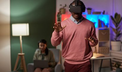 A man wears a VR headset, monitored by a researcher.