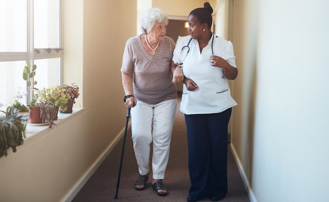Senior woman with walking stick being helped by a clinician.
