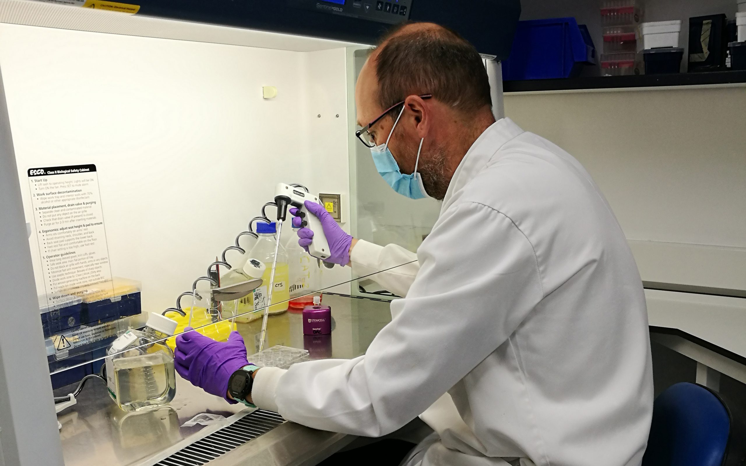 Andy Howden sits in a lab, working on an experiment.