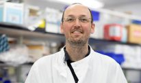 Research scientist Andy Howden smiles for a photo in a lab coat.
