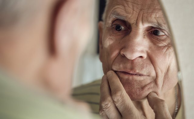 An older man looks closely at himself in the mirror.