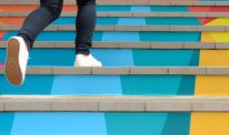A person runs up colourful stairs.